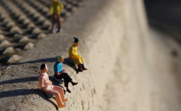 Miniature figures sitting on a curb