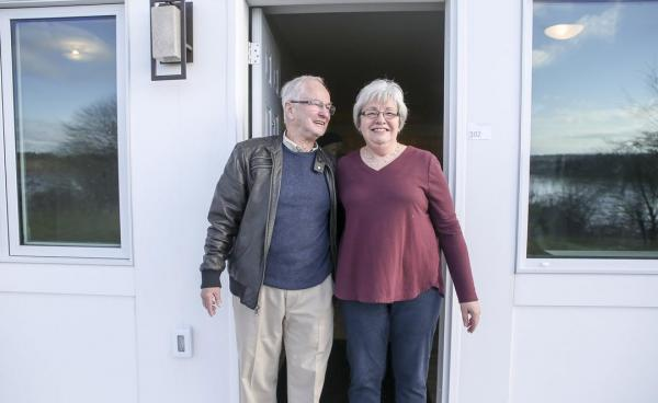 A happy older couple stands at the entrance to their house