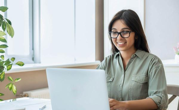 A women using a computer and smiling
